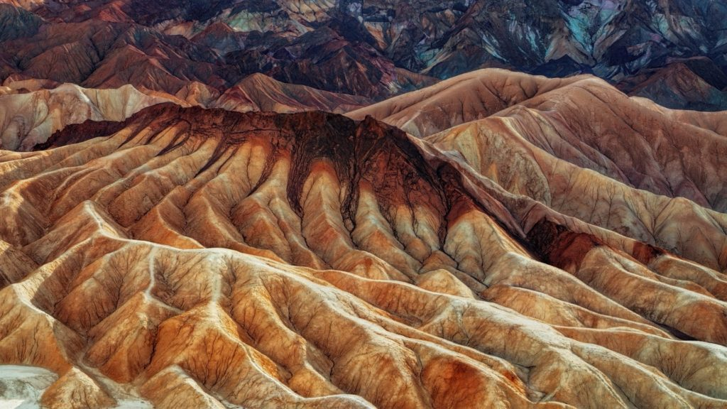 The multi-colored hills are from volcanic and sedimentary rock.